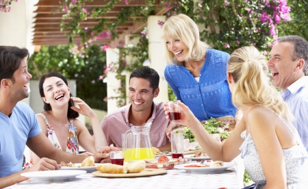 family meal: Group Of Young And Senior Couples Enjoying Family Meal