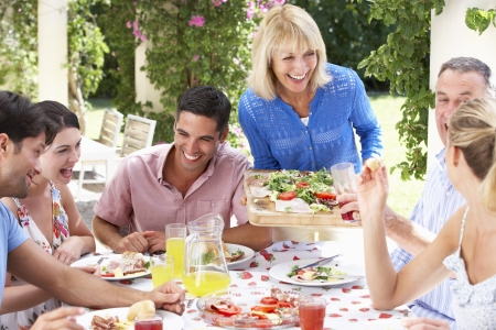 senior couples: Group Of Young And Senior Couples Enjoying Family Meal