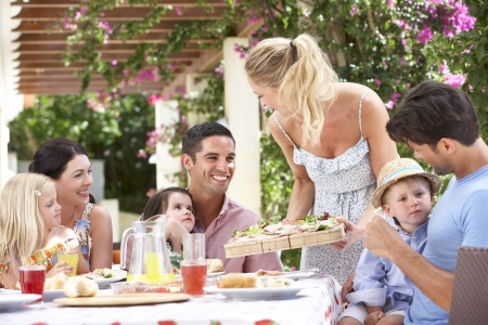 familia comiendo: Mujer sirviendo comidas a dos familias