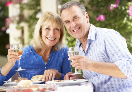 pareja comiendo: Senior pareja Disfrutar outdoorss comidas