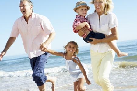 grandmother children: Abuelos y los nietos disfrutar de la playa para vacaciones