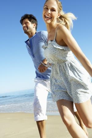 hombres corriendo: Pares que disfrutan de Romantic Beach