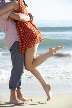 romantic hug: Couple Enjoying Romantic Beach Holiday Stock Photo