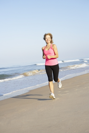 Senior Woman Exercising On Beach photo