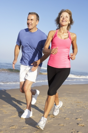 active holiday: Senior Couple Exercising On Beach Stock Photo