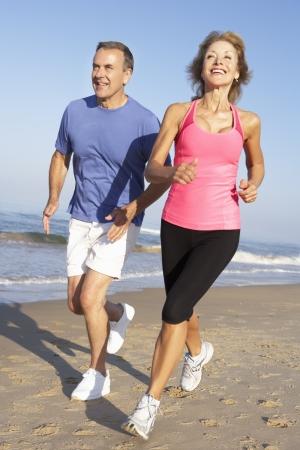 female jogger: Senior pareja Ejercicio En La Playa