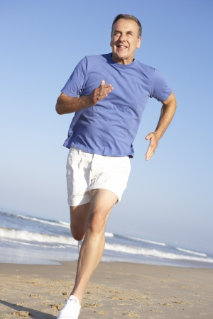 older men: Senior Man Exercising On Beach Stock Photo