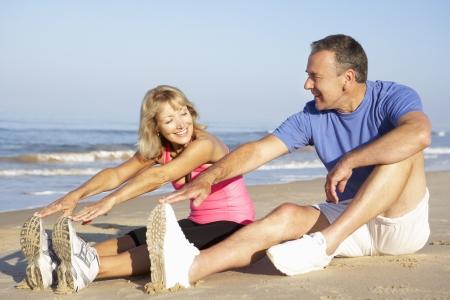 Senior Couple Exercising On Beach photo