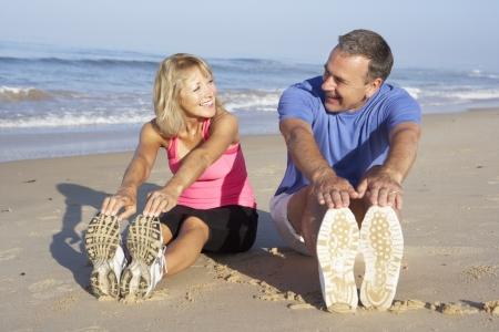 couple exercising: Senior Couple Exercising On Beach Stock Photo