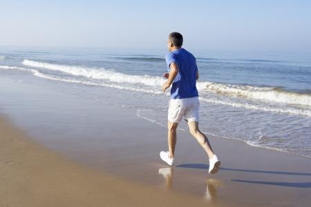 Senior Man Exercising On Beach photo