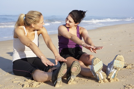 touching toes: Two Women Exercising On Beach