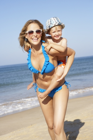 two year old: Mother And Son Running Along Beach Stock Photo