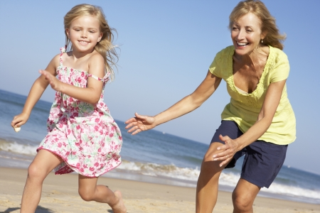 granddaughters: Grandmother And Granddaughter Running Along Beach