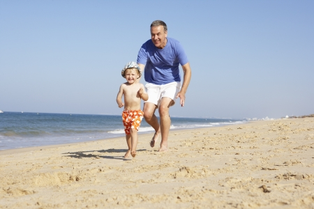 playing in the sea: Grandfather And Grandson Running Along Beach Stock Photo