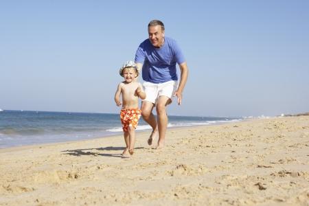 grandchild: Grandfather And Grandson Running Along Beach Stock Photo