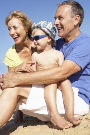 Grandparents And Grandson Sitting On Beach photo