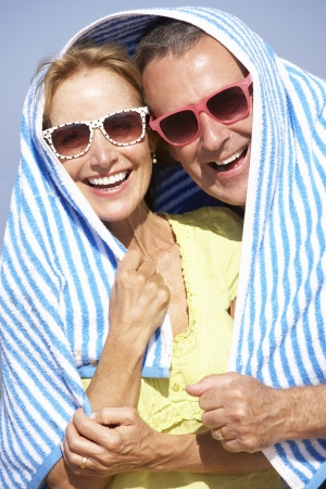 Senior Couple Sheltering From Sun On Beach Holiday photo