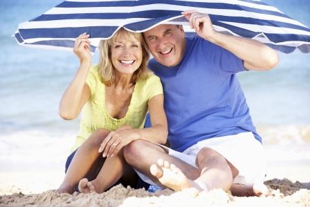 ombrellone spiaggia: Coppia Senior ripara dal sole sotto ombrellone Archivio Fotografico