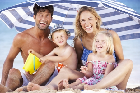 swimming at the beach: Family Sheltering From Sun Under Beach Umbrella