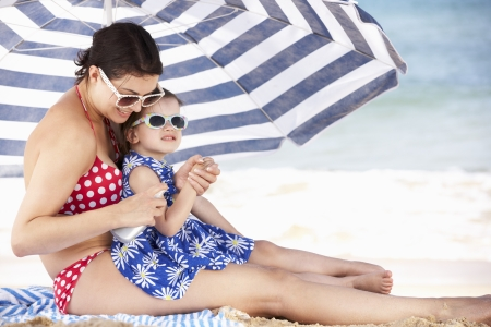 beach umbrella: Mother And Daughter Under Beach Umbrella Putting On Sun Cream Stock Photo
