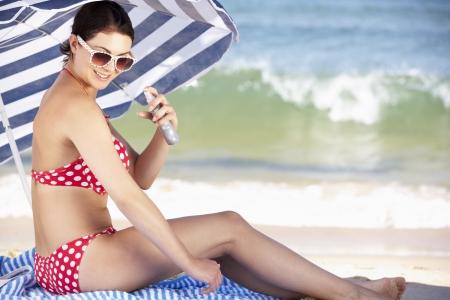 sheltering: Woman Sheltering From Sun Under Beach Umbrella Putting On Sun Cream
