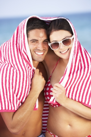 sheltering: Couple Sheltering From Sun On Beach Holiday Stock Photo