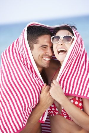 woman in towel: Couple Sheltering From Sun On Beach Holiday Stock Photo