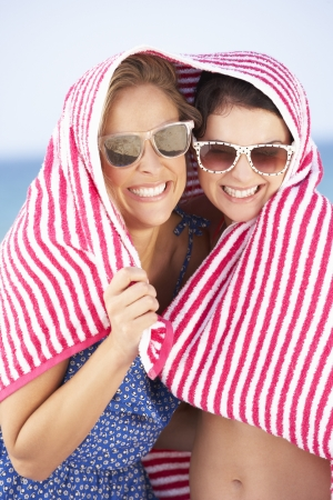 thirties portrait: Two Women Sheltering From Sun On Beach Holiday