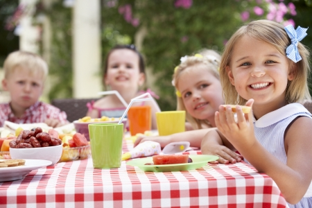 party friends: Group Of Children Enjoying Outdoor Tea Party Stock Photo