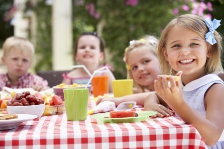 children party: Group Of Children Enjoying Outdoor Tea Party Stock Photo