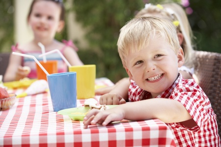 and four of the year: Group Of Children Enjoying Outdoor Tea Party Stock Photo