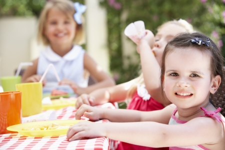 eating in the garden: Group Of Children Enjoying Outdoor Tea Party Stock Photo
