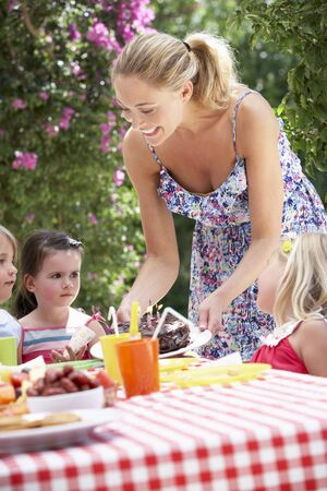 Mother Serving Birthday Cake To Group Of Children Outdoors photo