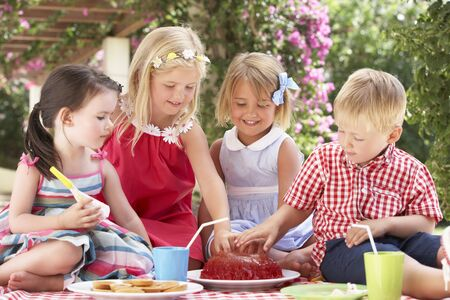 and four of the year: Group Of Children Eating Jelly At Outdoor Tea Party Stock Photo
