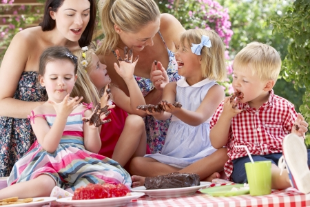 Children And Mothers Eating Jelly And Cake At Outdoor Tea Party photo