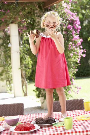 Girl Eating Jelly And Cake At Outdoor Tea Party Stock Photo - 18722626