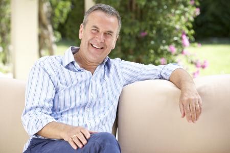Senior Man Relaxing On Sofa At Home photo