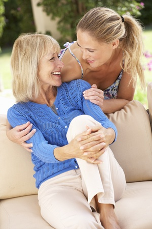 grown ups: Senior Woman With Adult Daughter Relaxing On Sofa At Home