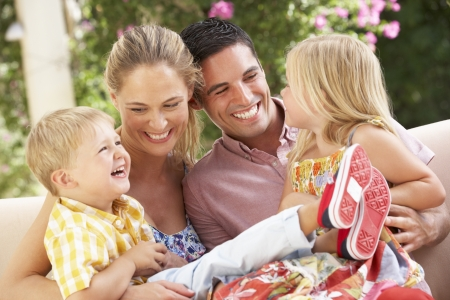 to cuddle: Family Sitting On Sofa Together Stock Photo