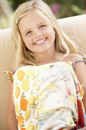 ni�os rubios: Muchacha feliz que se sienta en el sof� Foto de archivo