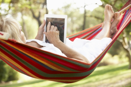 retirement: Senior Woman Relaxing In Hammock With  E-Book