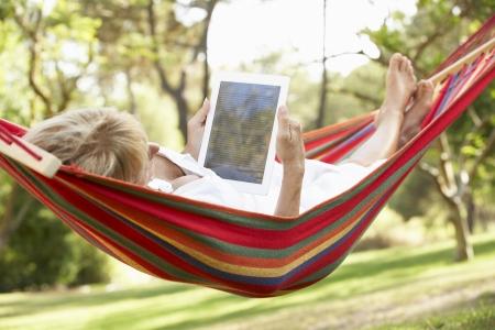 jubilados: Mujer mayor de relax en hamaca con E-Book