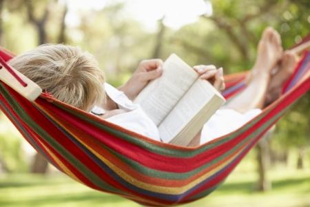 Senior Woman Relaxing In Hängematte Mit Buch Standard-Bild