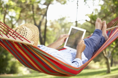 Senior Man Relaxing In Hammock With  E-Book Stock Photo