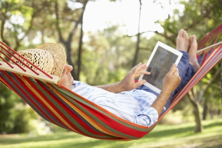 senior reading: Senior Man Ontspannen In Hangmat Met E-Book Stockfoto