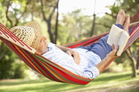 Senior Man Ontspannen In Hangmat Met Boek Stockfoto