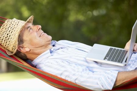 hamaca: Hombre mayor relax en hamaca con la computadora portátil Foto de archivo