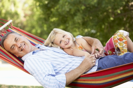 Grandfather And Granddaughter Relaxing In Hammock photo