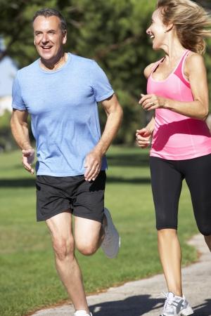 excercise: Senior Couple Exercising In Park Stock Photo