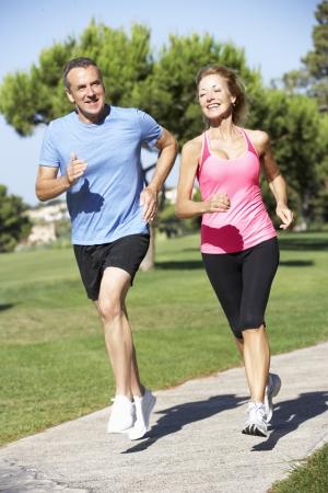 ジョグ: 公園で運動年配のカップル